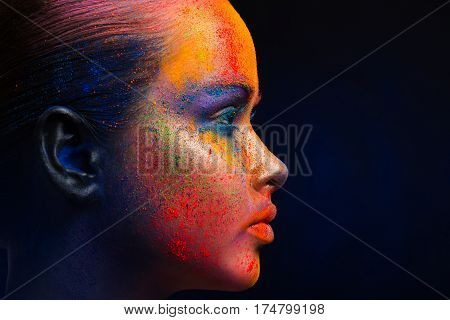 Holi festival of colors background. Female face art with creative make up. Closeup cropped studio portrait of young fashion model with bright colorful mix of paint. Profile on black with copy space