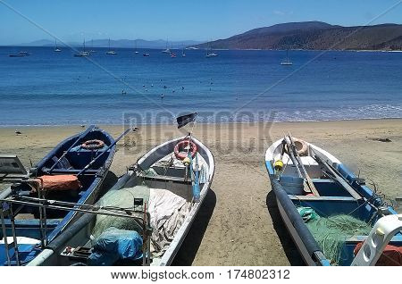 Fishing boats waiting to work at front of a calm sea in Papudo, Chile