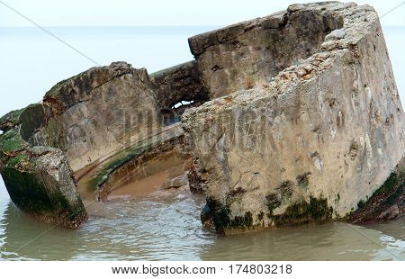 the ruined circular building of concrete on the sea shore