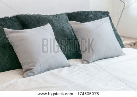 Bedroom Interior Design With Grey Pillows On White Bed And Decorative Table Lamp.