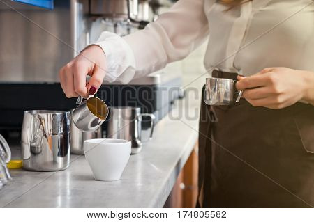 famale barista is preparing coffee on coffee machine
