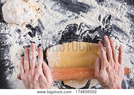 Baking concept. Flour, milk, butter, yeast and eggs carton on rustic wooden table, cooking ingredients. Unrecognizable man's hands top view roll out dough on black background. Male baker