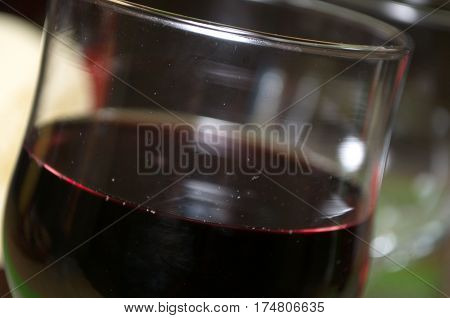 Half full glass of fresh delicious red wine, bottles in the background with heart, Novi Sad, Serbia