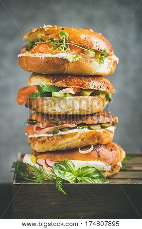 Heap of Bagels with salmon, eggs, vegetables, capers and cream-cheese, grey concrete background. Healthy breakfast, lunch or take-away food concept