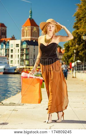 Spending money on sales buying things concept. Fashionable woman walking with shopping bags through the town wearing glamorous outfit and big sun hat