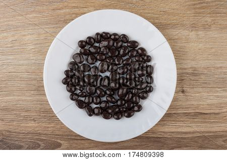 Dragee Raisins In Powder Cacao In White Plate On Table