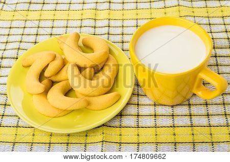Shortbread Cookies In Saucer, Yellow Cup Of Milk On Napkin