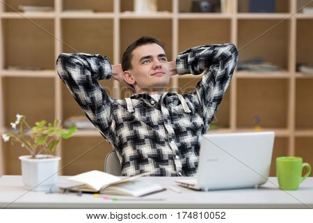 Happy young Man in casual Shirt sitting at grey working Place with Computer Flower Papers and Tea Mug relaxed smiling Face satisfied with good Job well done on wooden Wall Background.