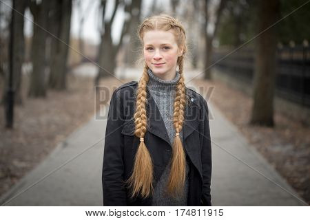 Red-haired girl with braids spring in nature