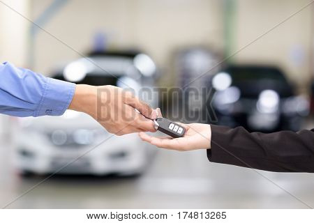 Young business women giving a key car in font of car