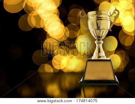 Trophies placed on a wooden table with gold light bokeh background copy space ready for your design.