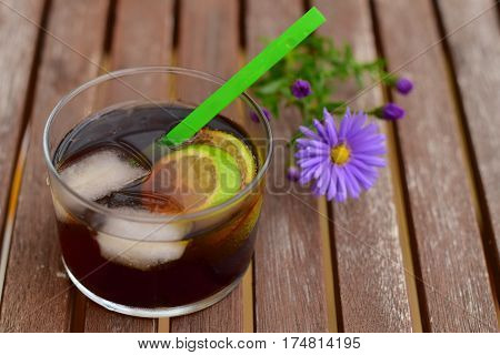 Cola lime drink mocktail in glass with ice cubes on wooden background