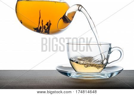 Pouring Tea From Teapot On Wooden Over White Background, Close Up