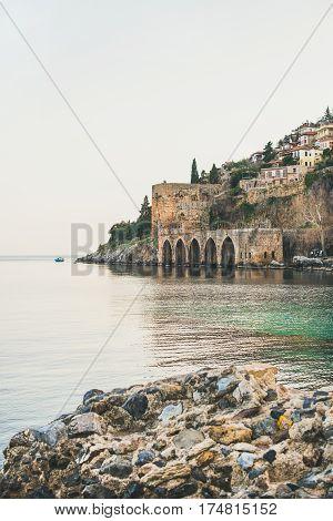 Alanya ancient medieval fortress towers, wall and shipyard and still Mediterranean sea, Turkey