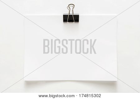 Blank empty sheet of paper attached with clip isolated on white background. Copy space