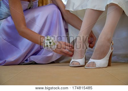 closeup of bride's white shoes and bridesmaid's hands. Morning routine bride