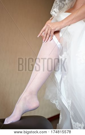 Bride in dressing gown is wearing bridal stockings indoors. Beautiful model girl in wedding clothes. Closeup arms of woman