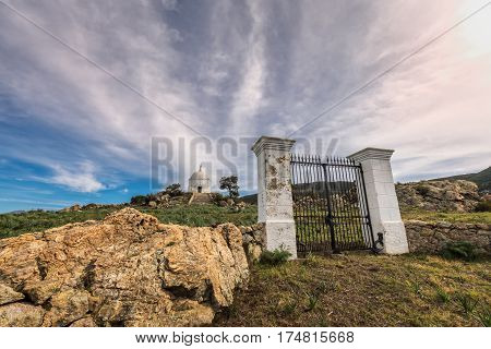 Wispy clouds above large iron gates and painted stone pillars leading to the steps to a large white domed mausoleum at Palasca in the Balagne region of Corsica