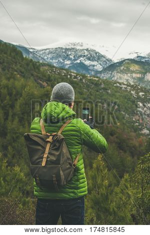 Young man traveller wearing bright jacket making photo of beautiful landscape with slopes and snowy mountains in Dim Cay district of Alanya, Antalya province, Mediterranean Turkey