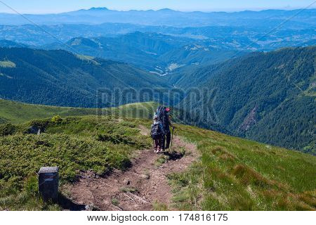 Travelers man and boy with backpacks descend along the ridge on the background of the panorama of green mountains on a sunny spring day. Back view.