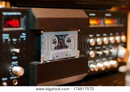 Old compact audio cassette in vintage audio system with tape recorder
