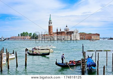 Venice Italy - June 14 2016: Water taxi's and Gondola's are busy in the harbor near St. Marks Square with Church of San Giorgio Maggiore in the background.
