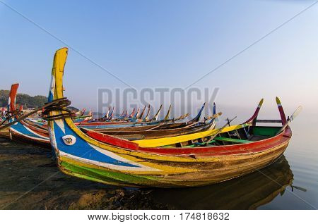 traditional boat at sunrise in Taungthaman Lake near the U Bein Bridge, Mandalay, Myanmar , selective focus, color tone effect.