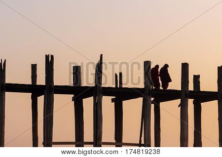 Silhouette of monk crossing on the longest bridge in the world, U-Bein Bridge, Mandalay, Myanmar.