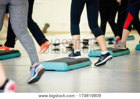 Women doing aerobic class with steppers to people group on fitness center detail of raised feet during aerobic step exercise at gym aerobics and people concept people working out with steppers in gym.