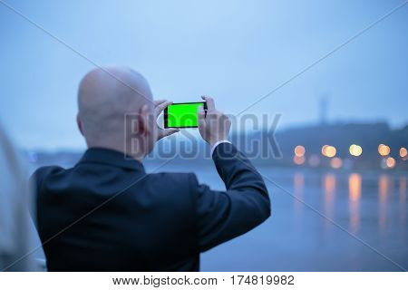 Back view of a bald businessman who taking a photo of coast landscape with smartphone at eveningMan taking photo of beautiful landscape with mobile phoneMiddle age male tourist making mobile photo .