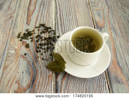 In a cup green tea is given. The white cup and a saucer are on a wooden table