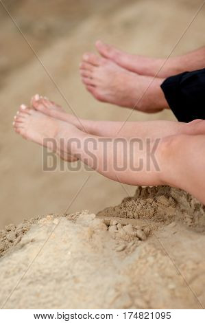 Barefoot girl and man sitting on sand. Couple having rest on sand quarry