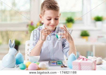 Happy child boy having fun during painting eggs for Easter in spring at home