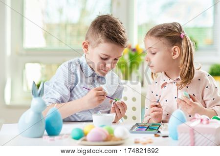 Two happy children having fun during painting eggs for Easter in spring time