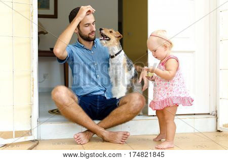 Dad and daughter and their dog. A man and a girl near her home on the porch. Next to them their pet.