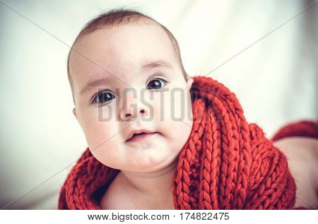 Portrait of a little girl wrapped in a large red scarf.