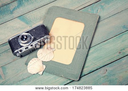 Old green photo frame with two sea shells and vintage camera on wooden background