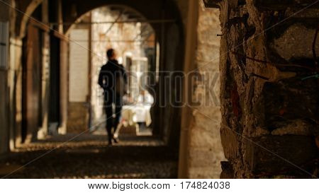 Young woman walking through the arches of the historical buildings away from the camera.