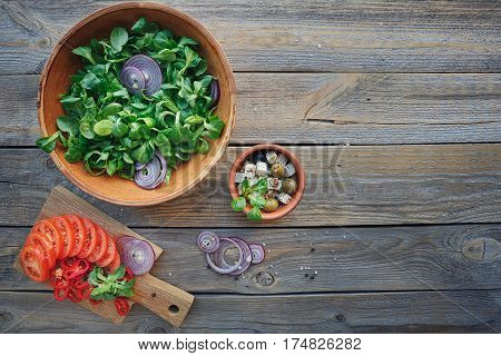 Ingredients for vegetables salad on a wooden background: lettuce leaves tomatoes red pepper onions olives oil and cheese. Top view with copy space.