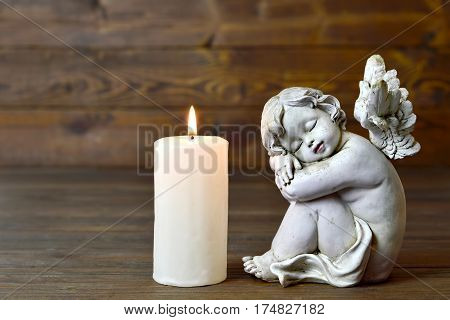 Angel figurine and white candle on wooden background