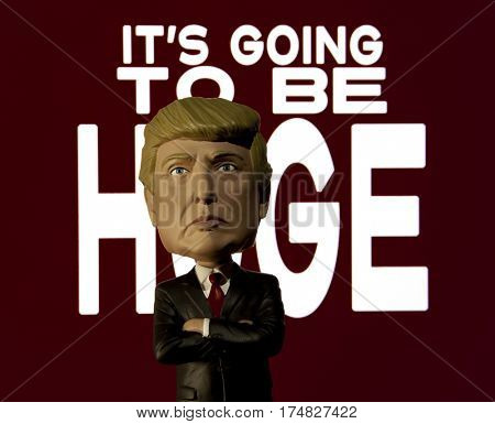 President Donald Trump Bobble head caricature figure standing in front of a sign reading It's Going to Be Huge - a Trumpism