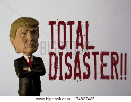 President Donald Trump Bobble head caricature figure standing in front of a sign reading Total Disaster - a Trumpism