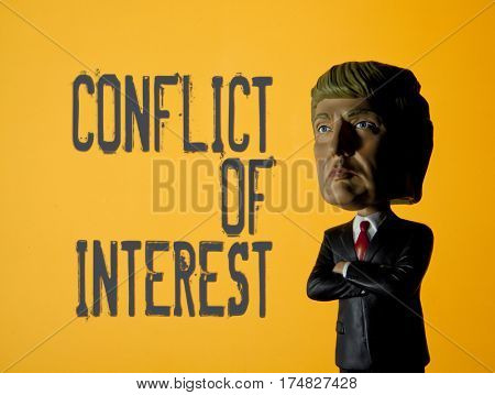 President Donald Trump Bobble head caricature figure standing in front of a sign reading Conflict of Interest - due to potential conflict between his business and with his title of US President