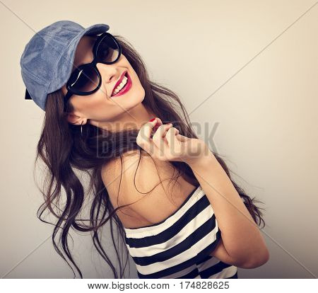 Enjoyment Young Woman In Sunglasses And Blue Baseball Cap Posing And Looking With Smile In Striped B