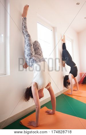 two young woman doing handstand by the window on fitness class healthy lifestyle concept
