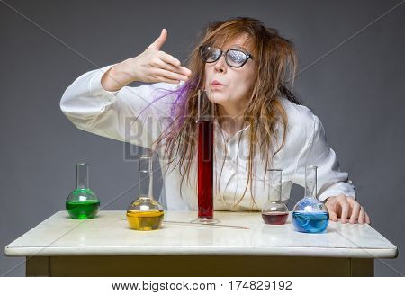 Sniffing shaggy chemist in lab on gray background