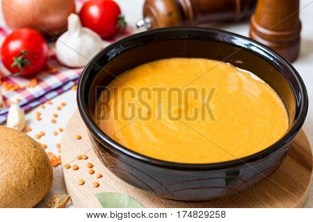 Red lentil cream soup in dark ceramic bowl on round cutting board. Grain lentils vegetables and bread. Vegetarian nutrition. Selective focus.