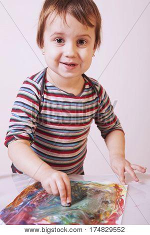 little girl learning to paint (child development in art training abilities)