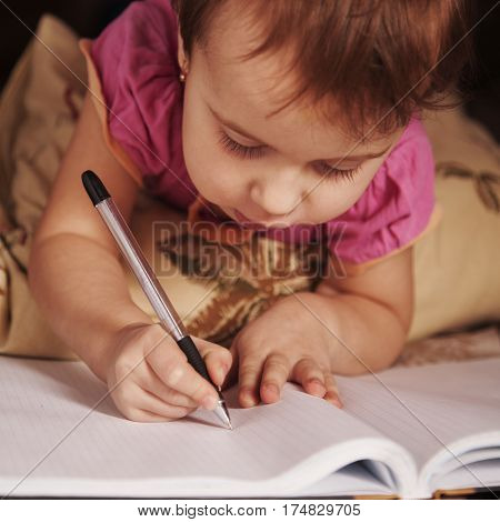 little baby girl learns to write (development training education concept)