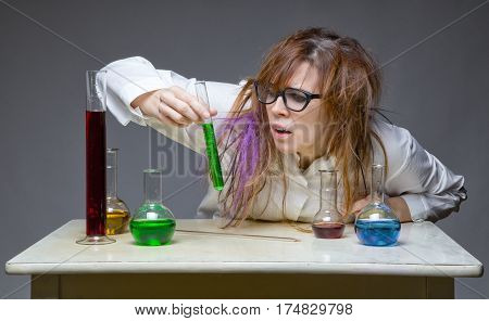 Surprised messy scientist in lab on gray background